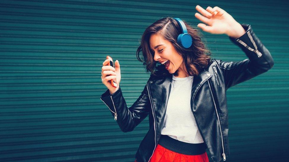 Una chica alegre bailando con cascos.