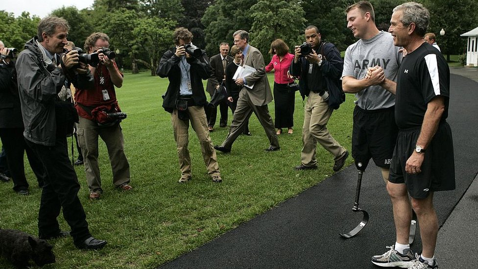 President George W Bush jogs around the White House with wounded veteran Christian Bagge on 2 June 2006