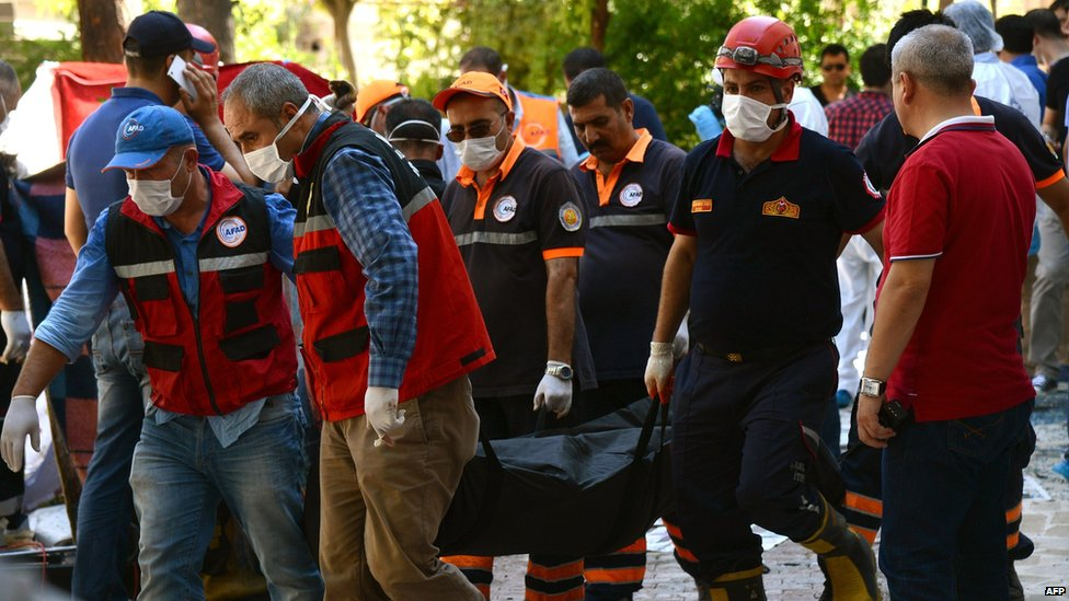Officials carry the bodies of victims after an explosion in the town of Suruc, Turkey (20 July 2015)