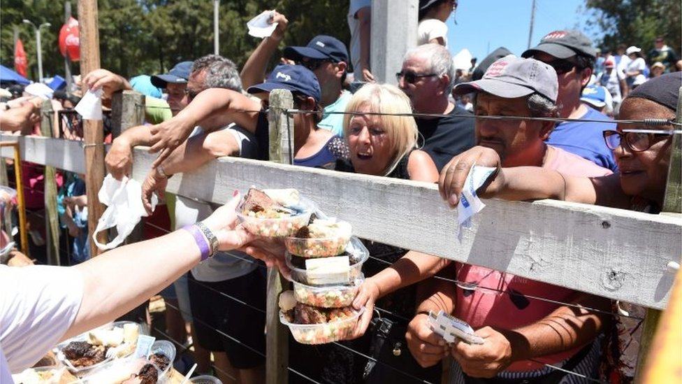 """Crowds wait for trays of barbecued beef as a total of 16,500 kg of beef are grilled in Rodo Park in Minas, Uruguay, 120 km from Montevideo, in an attempt to break the Guinness record for """"The World"""" s Biggest Barbecue"""", on December 10, 2017."""