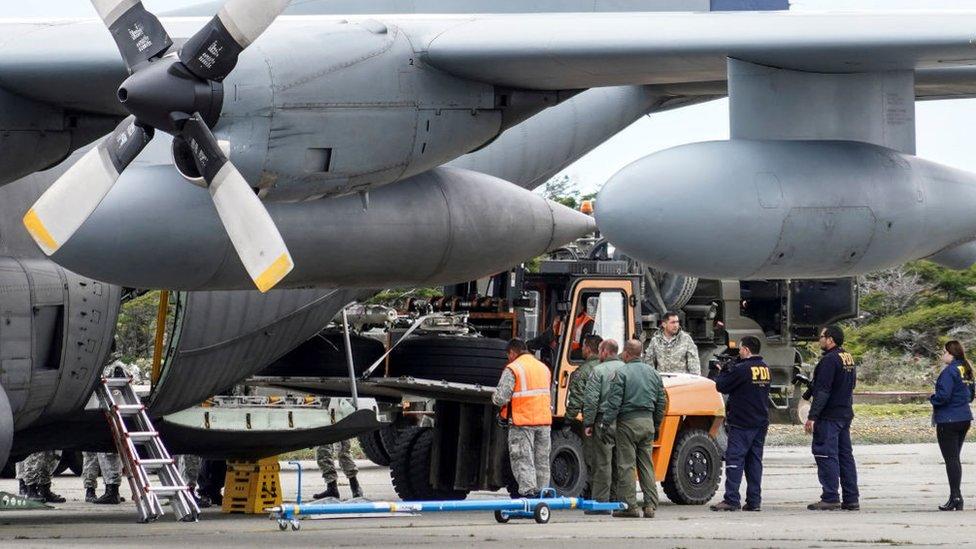 Personal militar de Chile descarga los restos encontrados del tren de aterrizaje del avión Hércules C-130.