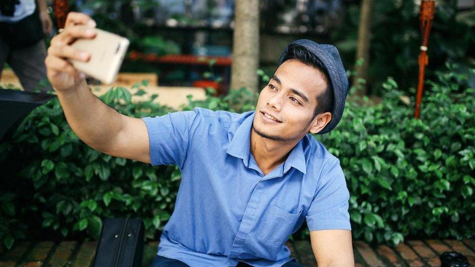 selfie çeken bir genç erkek