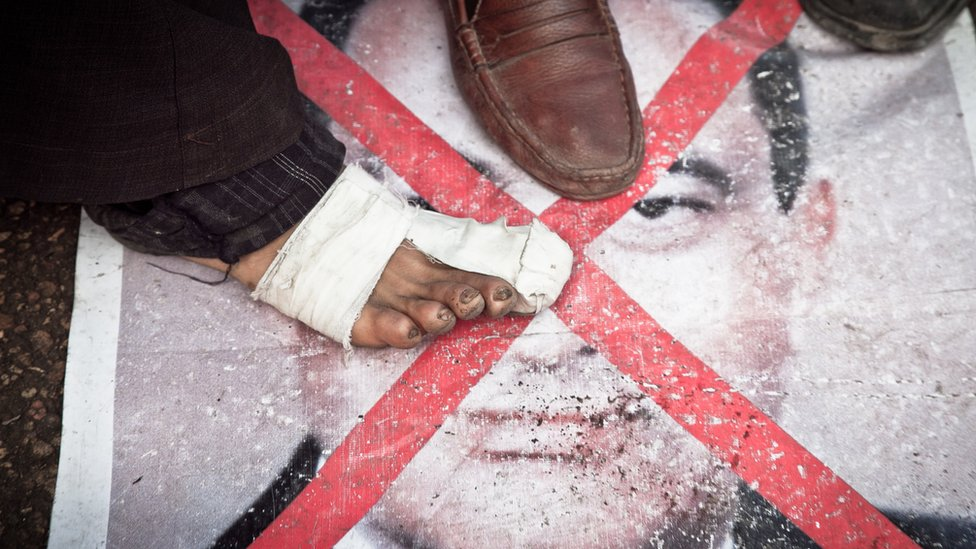 Protester stepping on poster of Mubarak