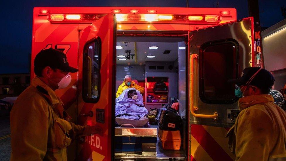 Dois paramédicos fecham as portas de uma ambulância, onde um terceiro paramédico atende um paciente encamado