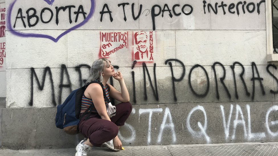 joven frente a pared con grafittis
