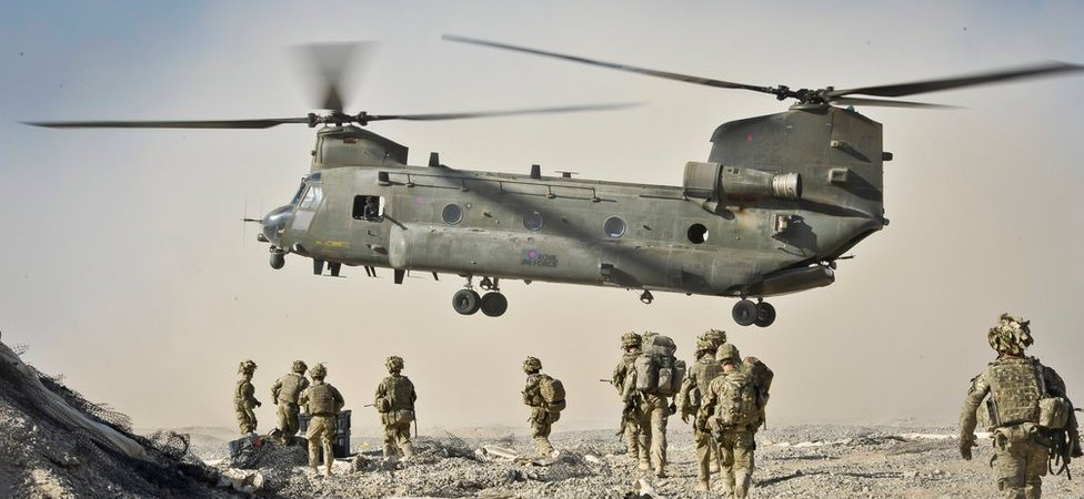 British troops approach an airborne Chinook aircraft in Afghanistan.