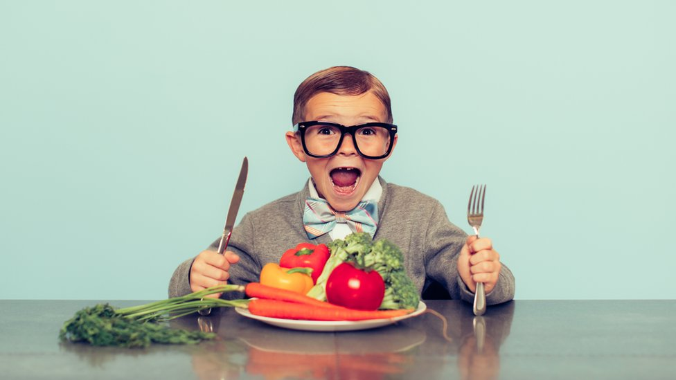Niño comiendo verduras.