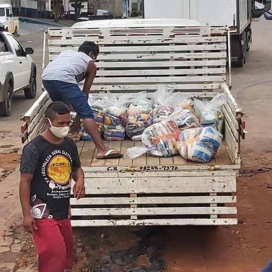 Dois homens em volta de caminhão com cestas básicas