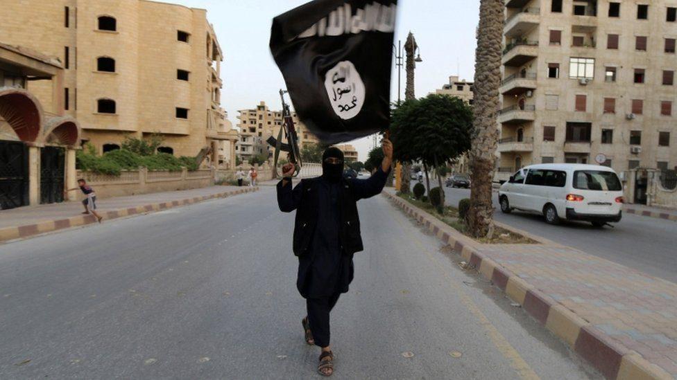 مسلح يرفع راية تنظيم الدولة