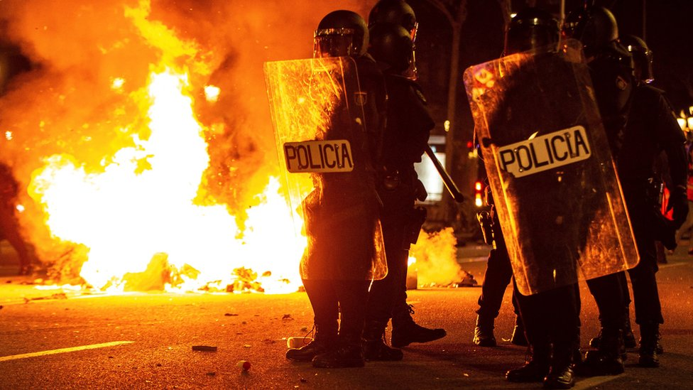 Policía antidisturbios en Barcelona, junto a un fuego.