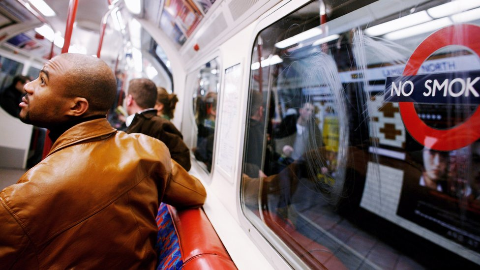 A passenger looks up at the Underground map