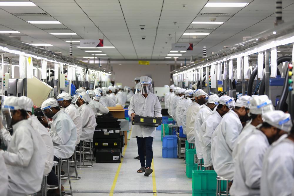 Hindistan'da fabrikaların tekrar açılmasıyla birlikte cep telefonu üretimi kaldığı yerden devam ediyor. Fakat yeni düzende işçilerin tamamı koruyucu ekipman giyiyor