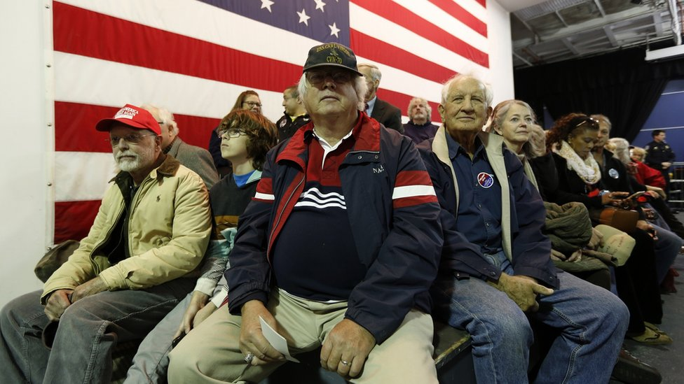 Donald Trump supporters sitting in front of an American flag