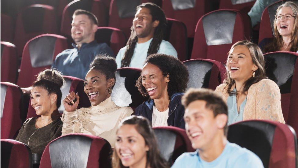 صورة لأشخاص يضحكون خلال جلوسهم على مقاعد مسرح