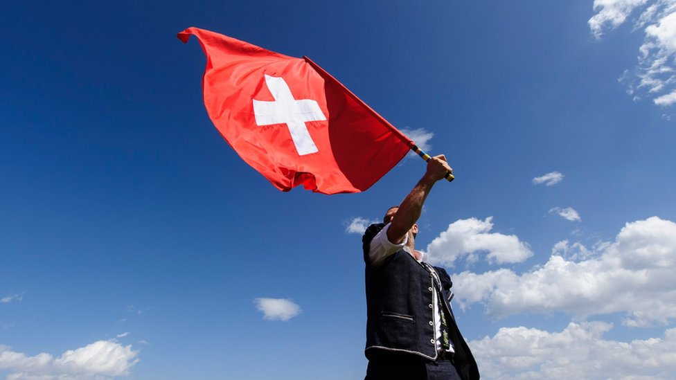 A man throws a Swiss flag on July 28, 2013 in Nendaz, Switzerland