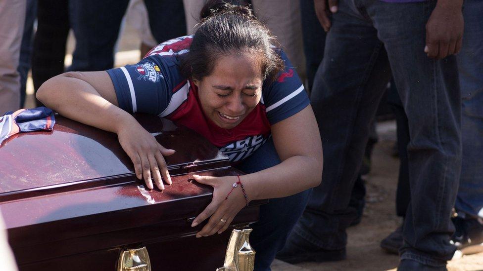 Mujer llorando sobre un féretro