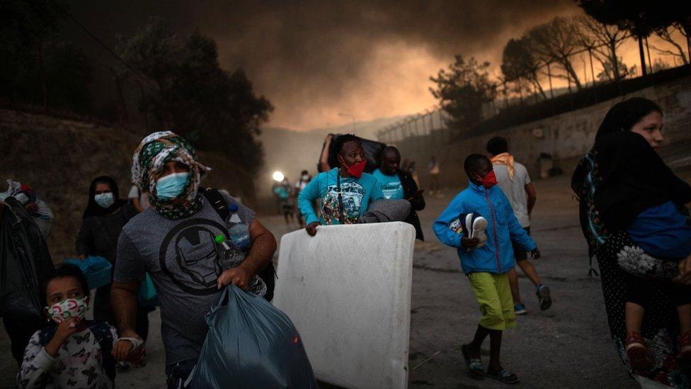 Refugiados y migrantes que llevan sus pertenencias huyen de un incendio en el campamento de Moria en la isla de Lesbos, Grecia, 9 de septiembre de 2020