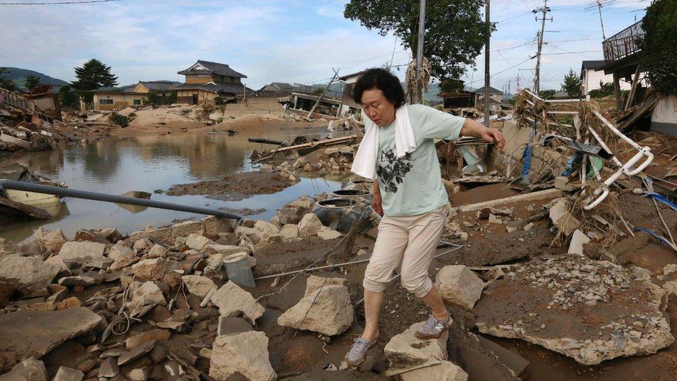 A resident walks across scattered debris in a flood hit area in Kurashiki, Okayama prefecture on July 9, 2018.
