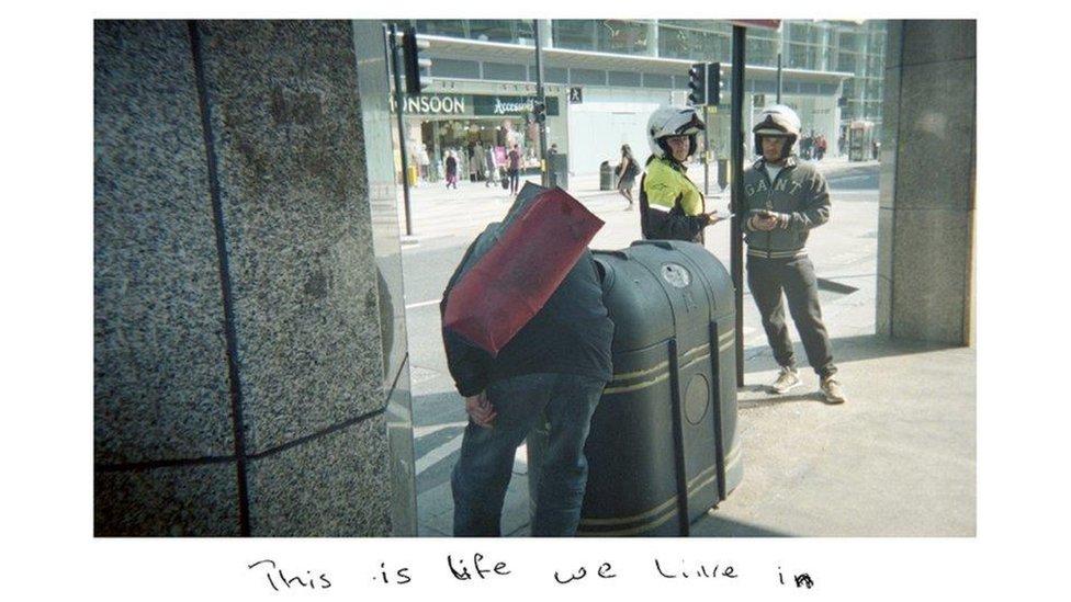 Sunny'nin çektiği fotoğraflardan birinde çöp karıştıran bir evsiz görülüyor ve fotoğrafın üzerinde