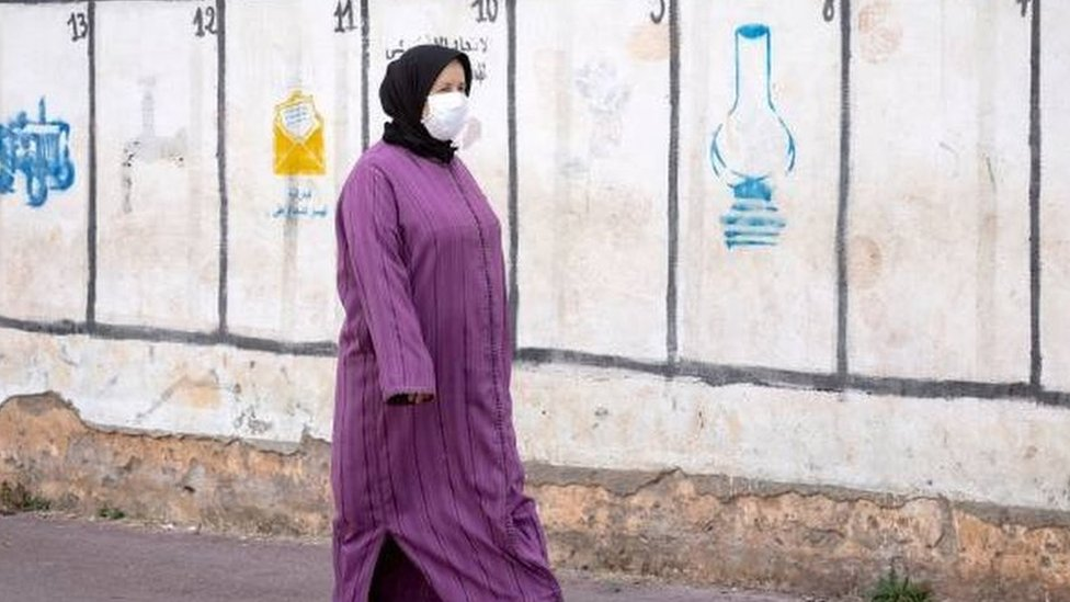 سيدة مغربية تمر قرب رموز انتخابية للمرشحين في الانتخابات البرلمانية المقبلة في العاصمة الرباط