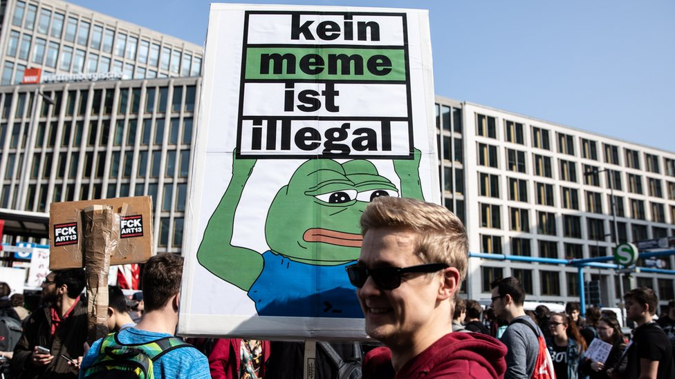 """A protestor holds a banner reading """"No meme is illegal"""" during the """"Save The Internet"""" demonstration in Berlin, Germany"""