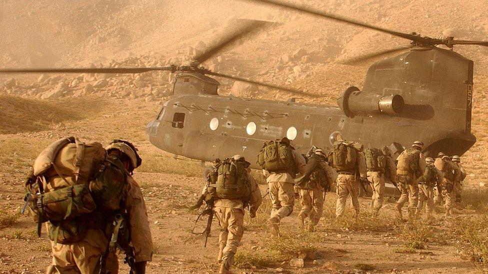 Soldados de la 10ma División de Infantería Ligera del ejército de EE.UU. abordan un helicóptero durante la invasión de Afganistán en 2001