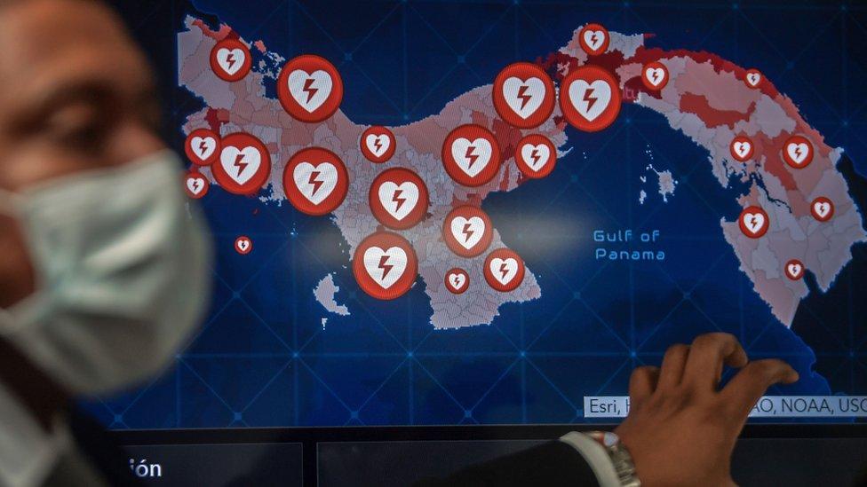 Un funcionario de salud de Panamá ante un mapa del país con puntos que marcan los centros de asistencia