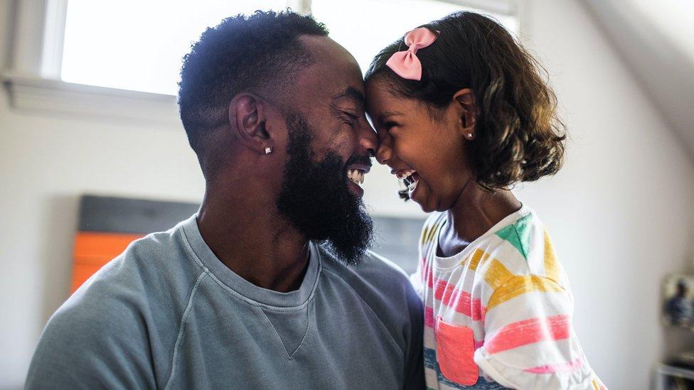 Père et fille riant dans la chambre à coucher