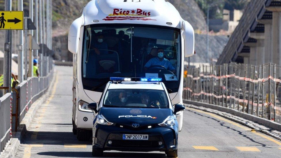 La policía española escolta a un autobús con marroquíes en un cruce fronterizo en Ceuta