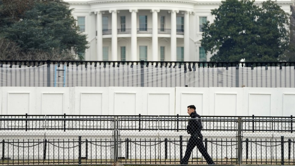 A member of the Secret Service walks along security fence installed around the White House