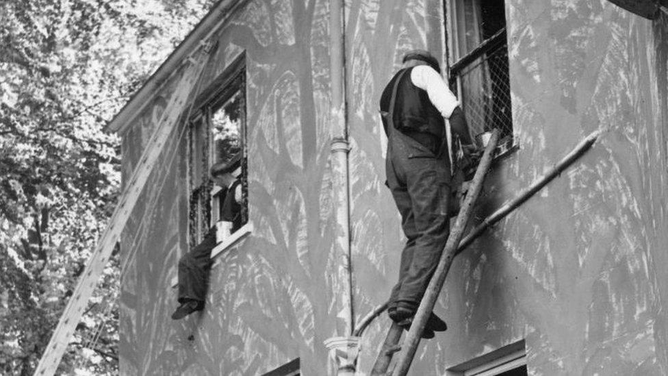 Pintores en la fachada de un edificio.