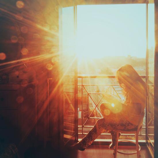 Una mujer sentada en un balcón con el Sol brillando fuertemente