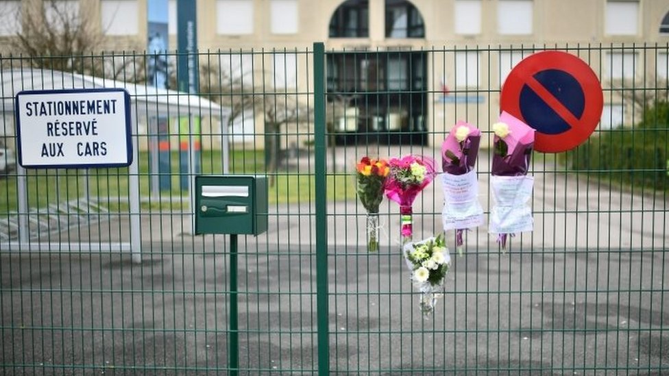 Flowers at the entrance of the school in Crepy-en-Valois, north-east of Paris, where a 60-year-old teacher who died infected with Covid-19 worked
