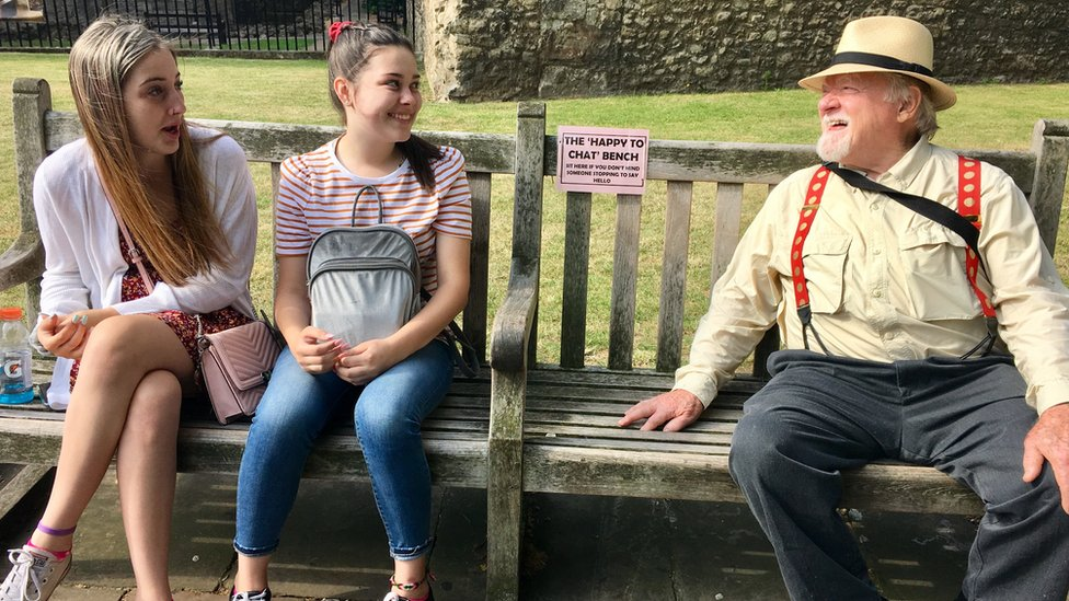 two young women and man on bench