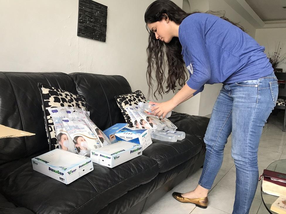 Rut Hernández acomodando paquetes en un sillón.