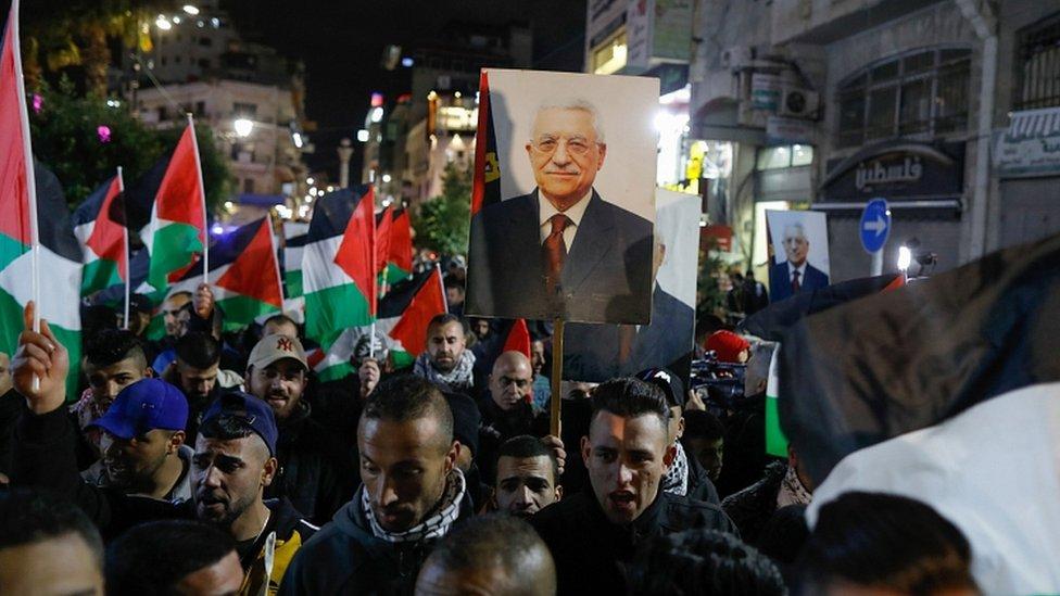 巴勒斯坦人遊行期間,舉著自治政府主席阿巴斯的畫像。
