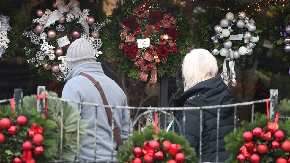 people looking at Christmas wreaths