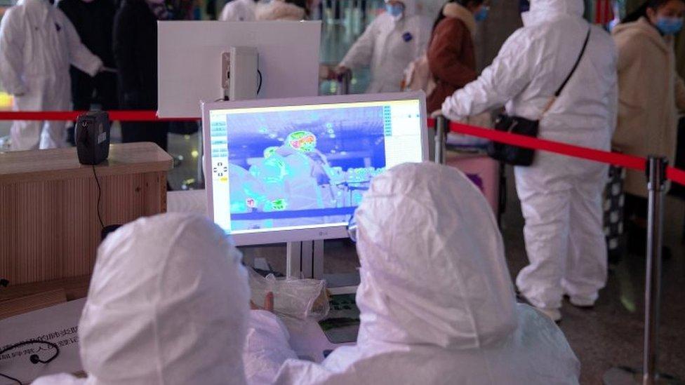 zaštitna odela i termalno skeniranje putnika na železničkoj stanici u kini, kineska nova godina 2020