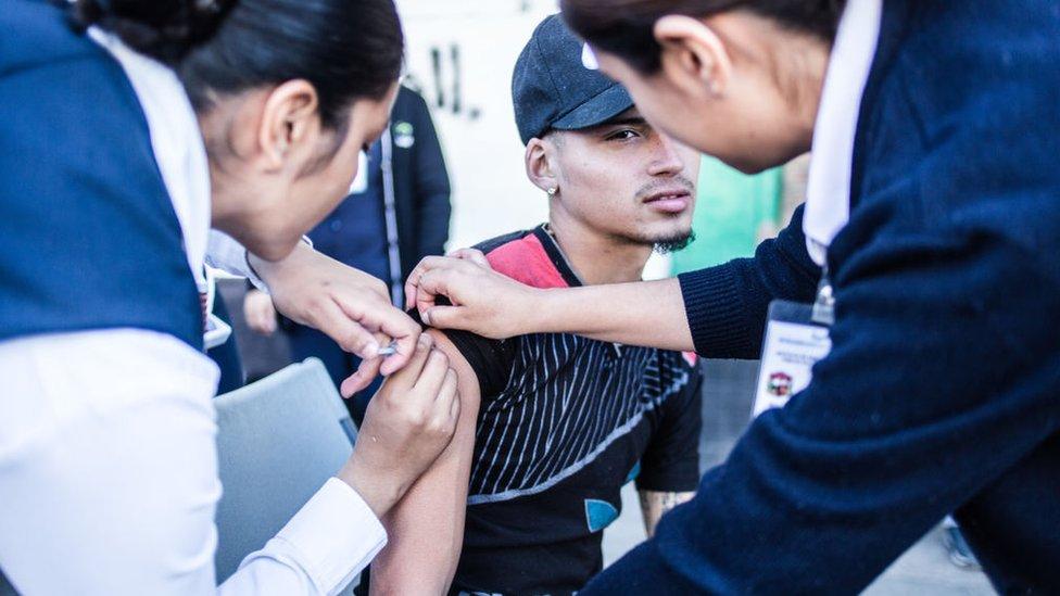 Un joven recibe una vacuna en el brazo