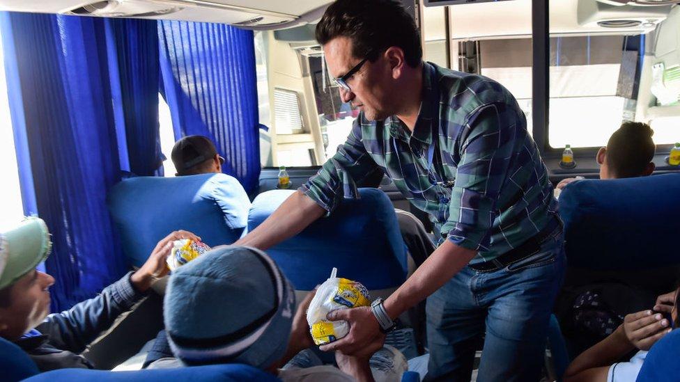 Benévolo repartiendo comida en un bus.