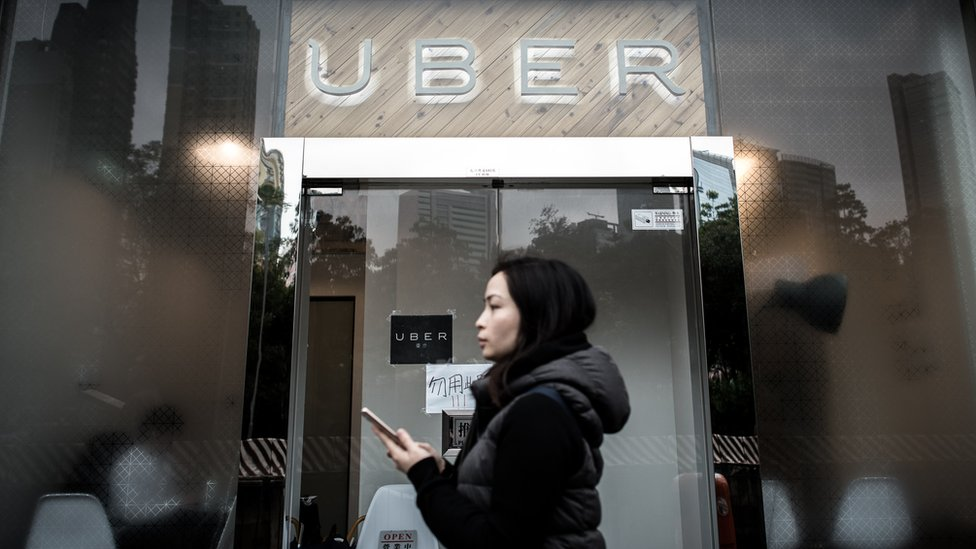A woman walks past the Uber offices in Hong Kong on January 22, 2016.