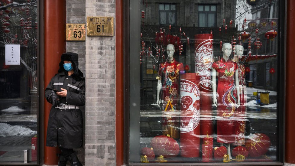 A guard stands outside a closed shop in Beijing