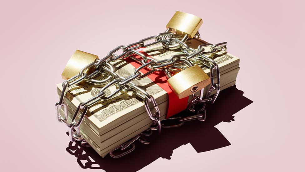 Dólares con cadenas y candados alrededor