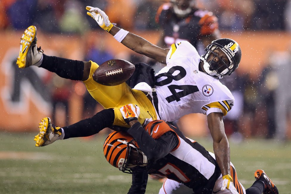 A Cincinatti Bengal player crunches into a Pittsburgh Steelers catcher