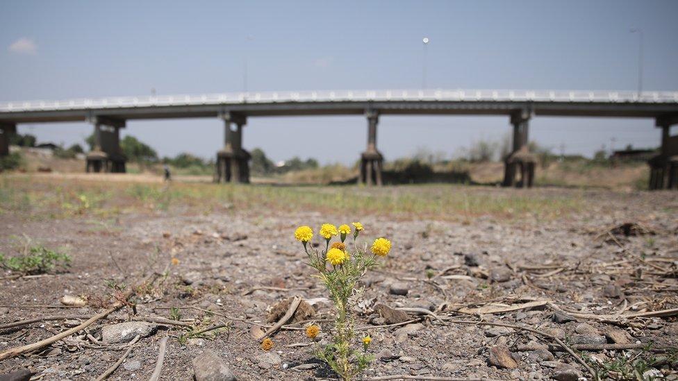 Imagem de terra seca, com uma ponte atrás