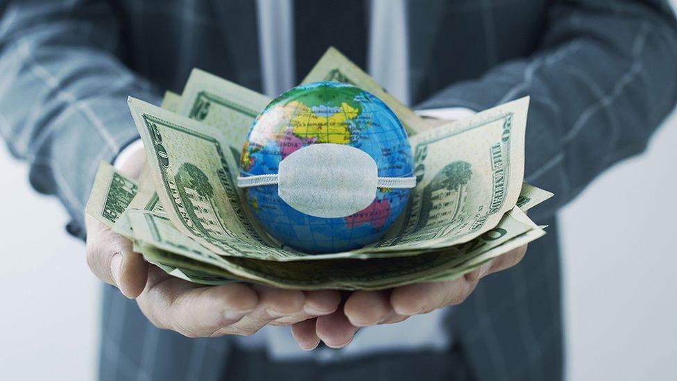 Un globo terráqueo con una mascarilla sobre billetes de dólares