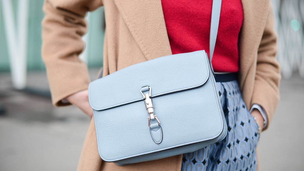 A woman wearing a handbag with a long strap across her should and body meaning her hands are free