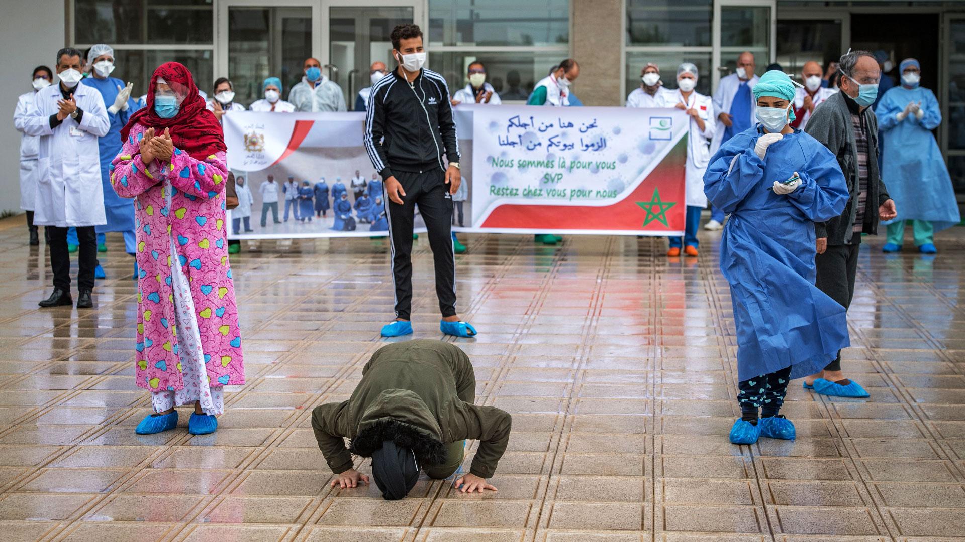 Un paciente de covid-19 besa el suelo tras abandonar el hospital en Marruecos.