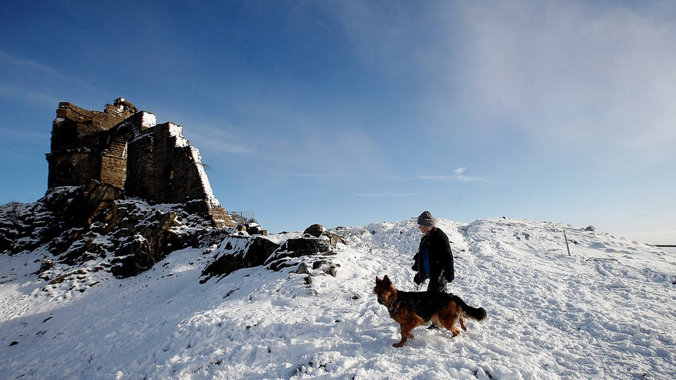 A woman walks her dog at Mow Cop Folly, Cheshire