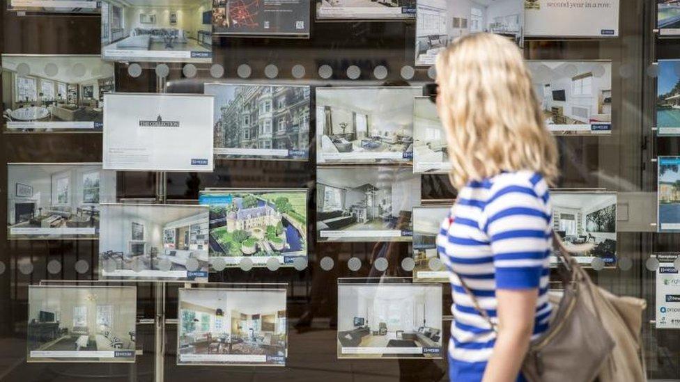 Woman looking in estate agents' window